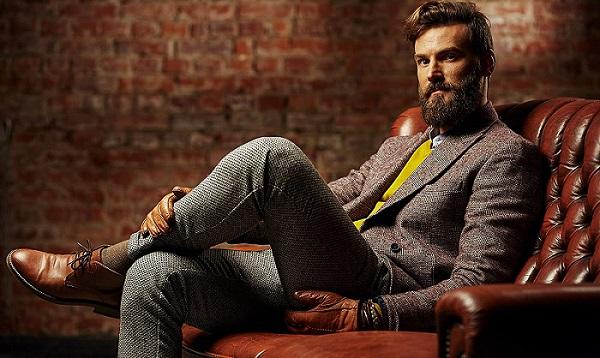 hombre con traje y jersey sentado en sillon