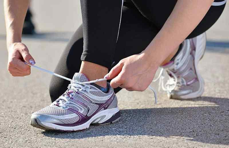 mujer se ata la zapatilla antes de correr